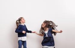 两个小女孩在演播室,握手,获得乐趣 免版税库存图片