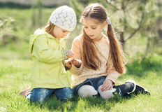 两个小女孩戏剧坐草坪 图库摄影