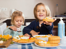 两个小女孩用奶油色点心 免版税图库摄影