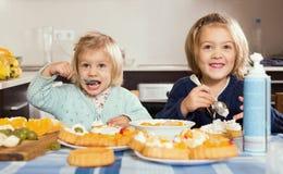 两个小女孩用奶油色点心 图库摄影