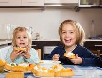 两个小女孩用奶油色点心 免版税库存照片