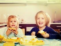 两个小女孩用奶油色点心 库存图片