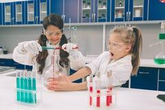 两个小孩在实验室在学校实验室涂上学会化学 防护玻璃做的年轻科学家 免版税库存照片