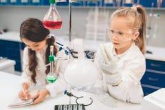 两个小孩在实验室在学校实验室涂上学会化学 防护玻璃做的年轻科学家 库存图片