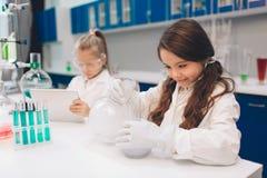 两个小孩在实验室在学校实验室涂上学会化学 防护玻璃做的年轻科学家 免版税图库摄影