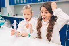两个小孩在实验室在学校实验室涂上学会化学 防护玻璃做的年轻科学家 免版税库存图片