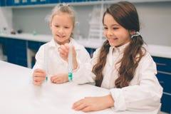 两个小孩在实验室在学校实验室涂上学会化学 防护玻璃做的年轻科学家 图库摄影