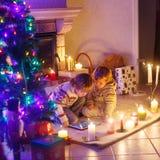 两个小孩在家由壁炉坐圣诞节 免版税图库摄影