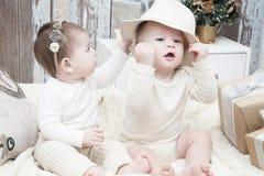 两个小孩子、一个男孩和一个女孩自然布料尿布的,自然包扎,环境友好的棉织物 免版税库存照片