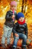 两个小孩男孩和女孩在秋天公园用在秋天附近的南瓜离开 免版税库存照片
