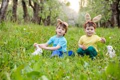 两个小孩男孩和朋友复活节兔子耳朵的在传统鸡蛋期间在春天庭院里寻找,户外 获得的兄弟姐妹乐趣 免版税图库摄影