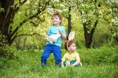 两个小孩男孩和朋友复活节兔子耳朵的在传统鸡蛋期间在春天庭院里寻找,户外 获得的兄弟姐妹乐趣 免版税库存图片