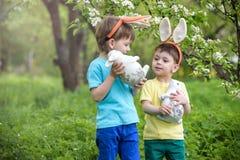 两个小孩男孩和朋友复活节兔子耳朵的在传统鸡蛋期间在春天庭院里寻找,户外 获得的兄弟姐妹乐趣 库存照片