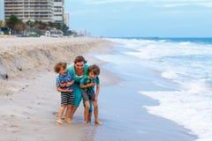 两个小孩男孩和母亲海滩的海洋 库存照片