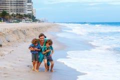 两个小孩男孩和母亲海滩的海洋 图库摄影