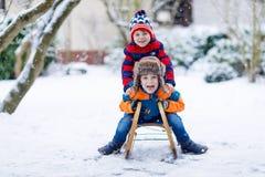 两个小孩男孩有乐趣雪橇乘驾在冬天 库存照片