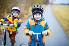 两个小孩男孩,乘坐在滑行车的最好的朋友在公园 库存照片