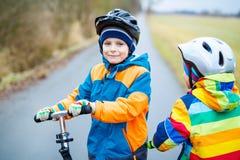 两个小孩男孩,乘坐在滑行车的最好的朋友在公园 图库摄影
