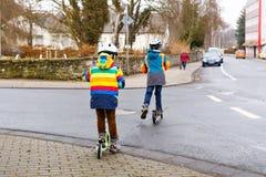 两个小孩男孩,乘坐在滑行车的最好的朋友在城市 库存照片