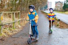两个小孩男孩,乘坐在滑行车的最好的朋友在城市 免版税库存照片