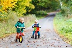 两个小孩获得在自行车的乐趣在秋天森林 库存照片