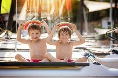 两个小孩,男孩兄弟,吃在beac的西瓜 免版税库存图片