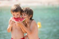 两个小孩,男孩兄弟,吃在beac的西瓜 免版税库存照片