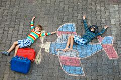 两个小孩,获得孩子的男孩与与飞机图片图画的乐趣与在沥青的五颜六色的白垩 朋友 库存照片