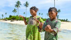 两个小当地姐妹一起跳舞和获得乐趣在海滩 免版税图库摄影