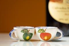 两个小杯子用饮用的苹果白兰地酒的被绘的苹果 库存照片