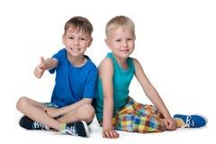 两个小男孩一起坐 免版税库存照片
