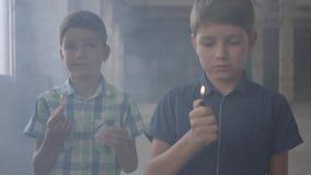 两个小男孩在一间发烟性被放弃的屋子 有一次灼烧的比赛的,第二一个男孩与一个灼烧的打火机 影视素材
