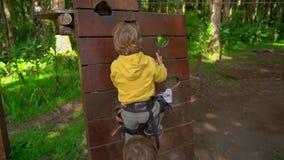 两个小男孩慢动作射击安全带的在森林冒险公园 室外娱乐中心与 影视素材