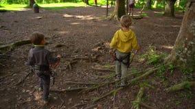 两个小男孩慢动作射击安全带的在森林冒险公园 室外娱乐中心与 股票视频