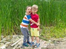 两个小男孩朋友在夏天晴天互相拥抱 Brot 库存图片