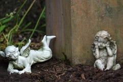 两个小的天使雕塑在小庭院里装饰 免版税库存图片