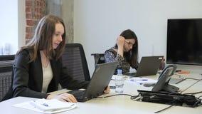 两个少妇严密地工作在膝上型计算机在办公室 股票视频