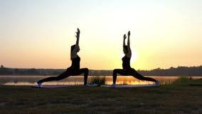 两个少妇做瑜伽战士锻炼在精采日落在Slo Mo 股票视频