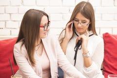 两个少妇在业务会议,在一个流动响度单位的谈话 免版税库存图片