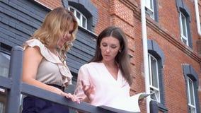 两个少妇在办公室阳台谈话关于交易的 沙发的妇女谈论物品样品 影视素材