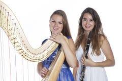 两个少妇在有竖琴和单簧管的演播室反对白色b 免版税图库摄影