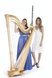 两个少妇在有竖琴和单簧管的演播室反对白色b 免版税库存图片