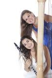 两个少妇在有竖琴和单簧管的演播室反对白色b 库存照片