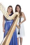两个少妇在有竖琴和单簧管的演播室反对白色b 库存图片