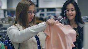 两个少妇在选择温暖的衣裳的商店购物 股票视频