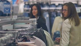 两个少妇在选择温暖的衣裳的商店购物 股票录像