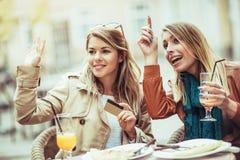 两个少妇在餐馆户外付帐 图库摄影