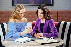 两个少妇在餐馆讨论看电话的企业问题 免版税库存图片