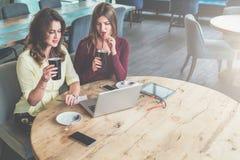 两个少妇坐在咖啡馆,饮用的咖啡的圆的木桌上并且看膝上型计算机屏幕 库存图片