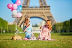 两个少妇有野餐在埃佛尔铁塔附近在巴黎,法国 库存图片